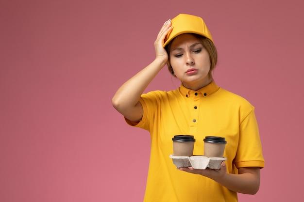 Mensageira de frente para mulher com capa amarela uniforme segurando copos de café de plástico em trabalho de entrega uniforme de fundo rosa