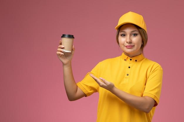 Mensageira de frente para mulher com capa amarela uniforme segurando xícara de café de plástico na cor de trabalho de entrega uniforme de fundo rosa