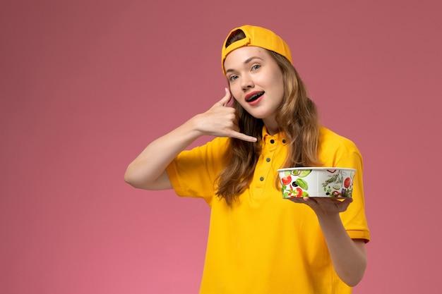 Mensageira de frente para mulher em uniforme amarelo e capa segurando a tigela de entrega na parede rosa.
