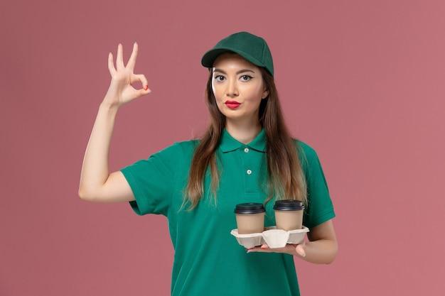 Mensageira de frente para mulher em uniforme verde e capa segurando xícaras de café de entrega na mesa rosa-claro empresa serviço trabalho uniforme entrega