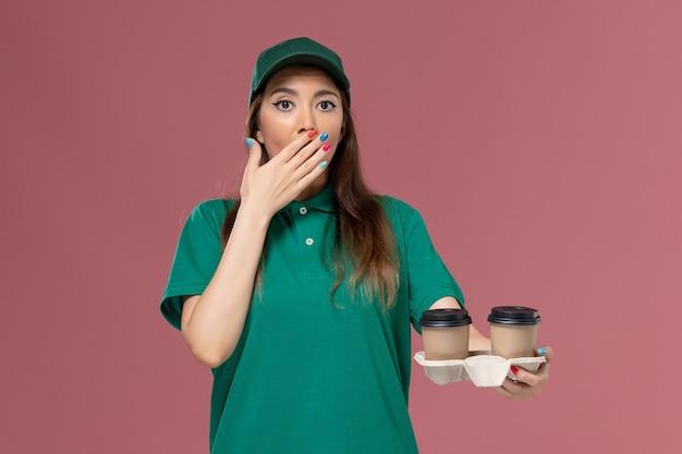 Mensageira de frente para mulher em uniforme verde e capa segurando xícaras de café de entrega na parede rosa claro empresa serviço trabalho uniforme entrega