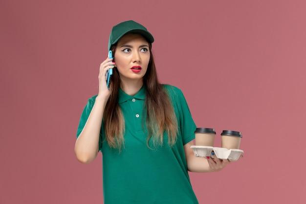 Mensageira de frente para mulher em uniforme verde e capa segurando xícaras de café e o telefone na mesa rosa.