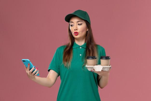 Mensageira de frente para mulher em uniforme verde e capa segurando xícaras de café e telefone na parede rosa claro.