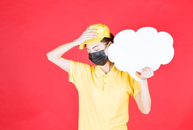 Mensageira de uniforme amarelo e máscara preta segurando um quadro de informações em forma de nuvem e parecendo cansada e com sono