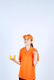 Mensageira de uniforme amarelo segurando um copo de macarrão para viagem e sentindo o cheiro do gosto
