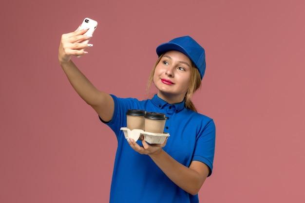Mensageira de uniforme azul segurando xícaras de café e tirando uma selfie rosa, serviço de entrega de uniforme de trabalho de trabalhador
