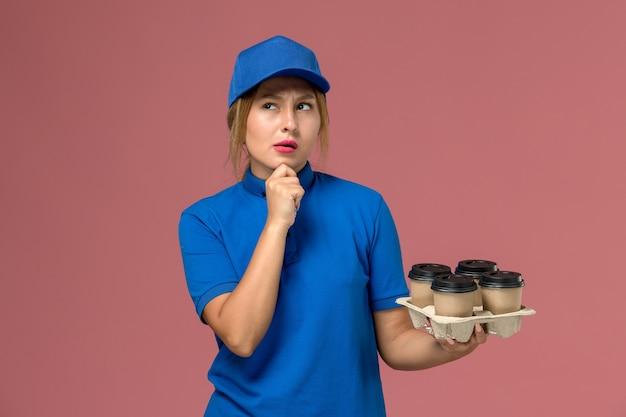 Mensageira de uniforme azul segurando xícaras de café marrom pensando na rosa, trabalhador de trabalho de entrega de uniforme de serviço
