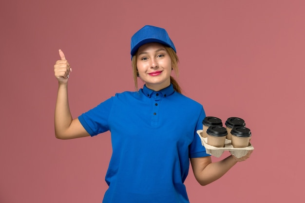 Mensageira de uniforme azul segurando xícaras de café marrons com um leve sorriso na rosa, trabalhador de trabalho de entrega de uniforme de serviço