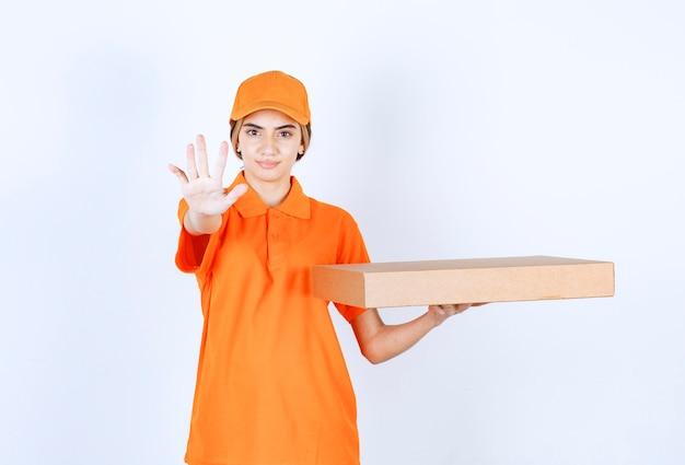 Mensageira de uniforme laranja entregando uma caixa de papelão e parando alguém