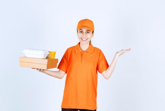 Mensageira de uniforme laranja segurando uma caixa de papelão, uma caixa de plástico para viagem e um copo de macarrão amarelo