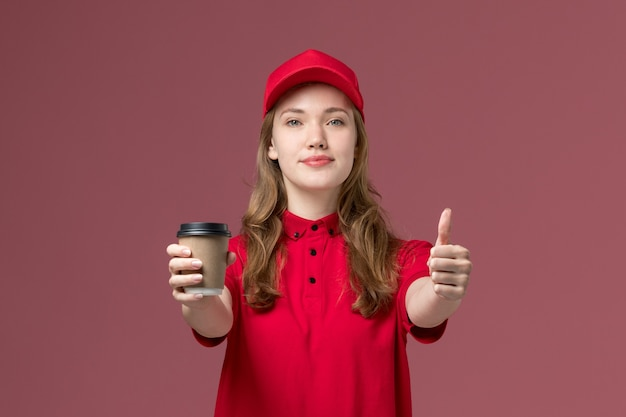 Mensageira de uniforme vermelho segurando a xícara de café posando em rosa claro, entrega de trabalhador de serviço uniforme de trabalho