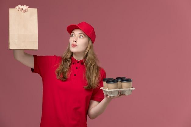 Mensageira de uniforme vermelho segurando copos de café de entrega com pacote de comida de papel rosa, uniforme de trabalho.