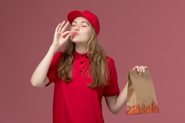 Mensageira de uniforme vermelho segurando pacote de comida de papel na rosa, entrega de serviço de trabalhador uniforme de trabalho