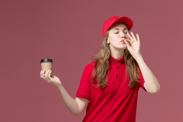 Mensageira de uniforme vermelho segurando uma xícara de café marrom mostrando um sinal saboroso em rosa-claro, serviço de trabalhador uniforme de trabalho