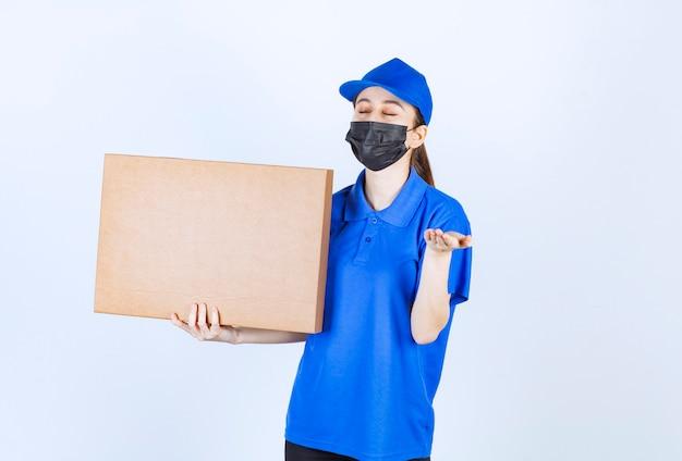 Mensageira feminina com máscara e uniforme azul segurando um grande pacote de papelão e cheirando o produto