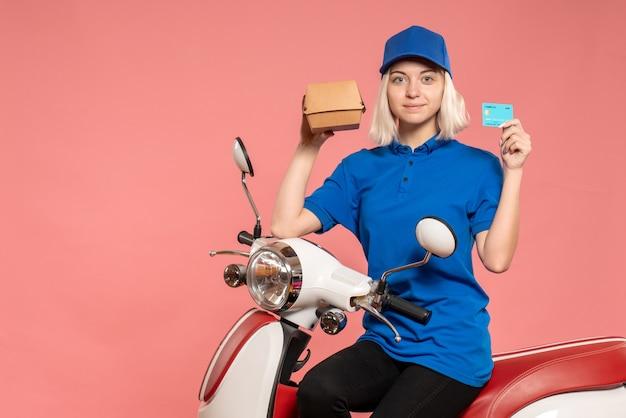 Mensageira feminina de frente em bicicleta com um pequeno pacote de comida e cartão do banco rosa