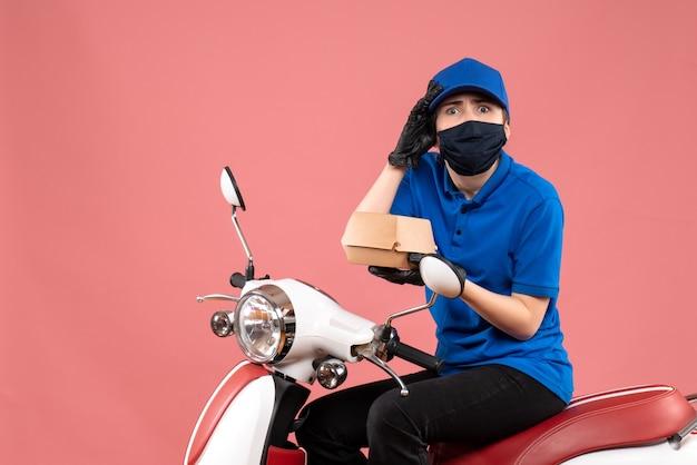 Mensageira feminina de vista frontal com máscara e pouco pacote de comida na rosa