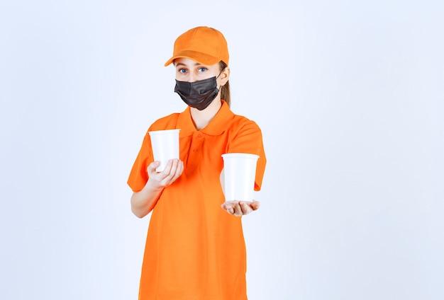 Mensageira feminina em uniforme amarelo e máscara preta segurando bebidas para viagem em copos de plástico com as duas mãos e oferecendo-as ao cliente.