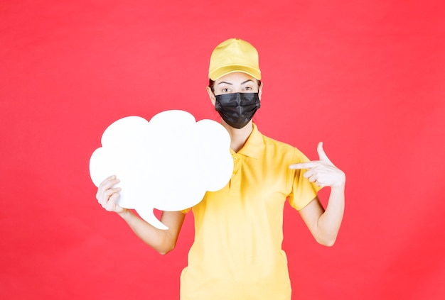 Mensageira feminina em uniforme amarelo e máscara preta segurando um quadro de informações em forma de nuvem e apontando para ele