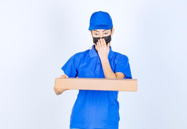 Mensageira feminina em uniforme azul e máscara facial segurando uma caixa de papelão e parece apavorada ou confusa.