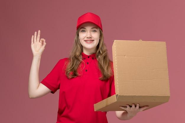 Mensageira feminina em uniforme vermelho segurando uma caixa de entrega de comida abrindo-a sorrindo em rosa claro, garota de serviço de trabalho uniforme