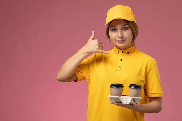 Mensageira frontal feminina com capa amarela uniforme segurando um copo de café marrom de plástico na mesa rosa uniforme feminino entregador