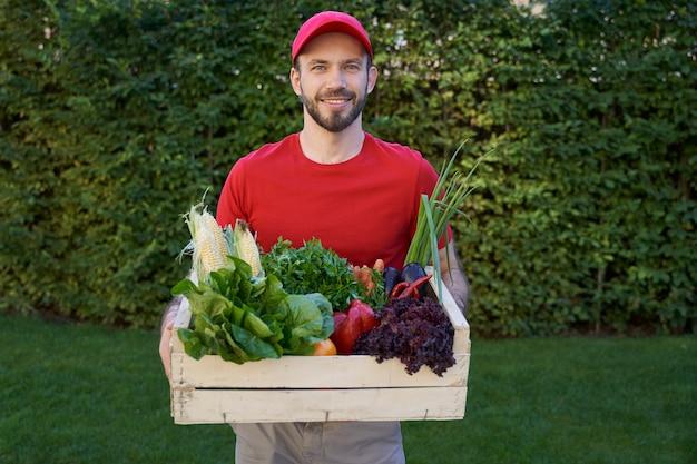 Mensageiro alegre segurando uma caixa de supermercado com legumes frescos