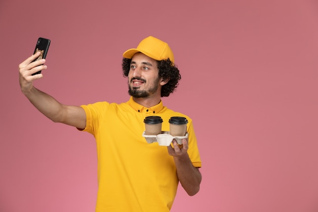 Mensageiro de frente com uniforme amarelo e capa segurando xícaras de café marrom tirando foto na parede rosa