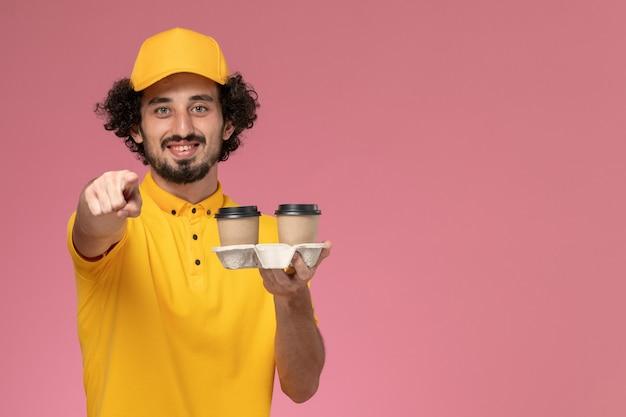 Mensageiro de frente com uniforme amarelo e capa segurando xícaras de café marrons com um sorriso na parede rosa