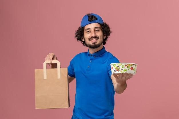 Mensageiro de frente com uniforme azul e capa segurando pacote de comida de entrega e tigela na parede rosa trabalho de uniforme de serviço de entrega