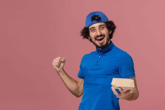 Mensageiro de frente com uniforme azul e capa segurando um pequeno pacote de comida para entrega e regozijando-se com a empresa de serviço de entrega de uniforme de parede rosa