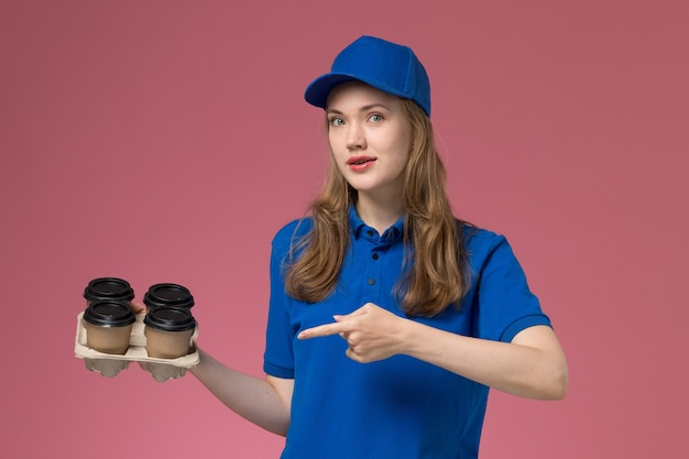 Mensageiro de frente com uniforme azul segurando xícaras de café marrom apontando na mesa rosa uniforme de serviço da empresa trabalhador