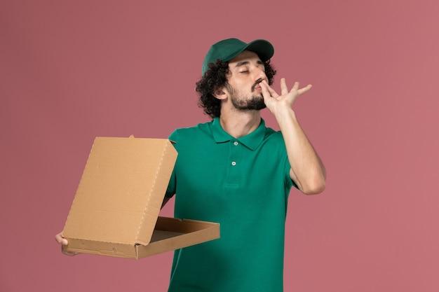 Mensageiro de frente com uniforme verde e capa segurando a caixa de entrega de comida no fundo rosa claro serviço trabalhador uniforme trabalho de entrega