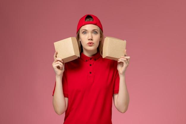 Mensageiro de frente com uniforme vermelho e capa segurando pequenos pacotes de comida de entrega na parede rosa claro, trabalhador de entrega de uniforme