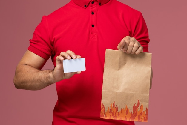 Mensageiro de frente de perto com uniforme vermelho e capa segurando o pacote de comida e o cartão na parede rosa