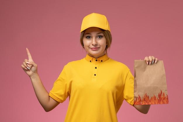 Mensageiro de frente para mulher em uniforme amarelo capa amarela segurando pacote de comida no fundo rosa uniforme entrega trabalho cor