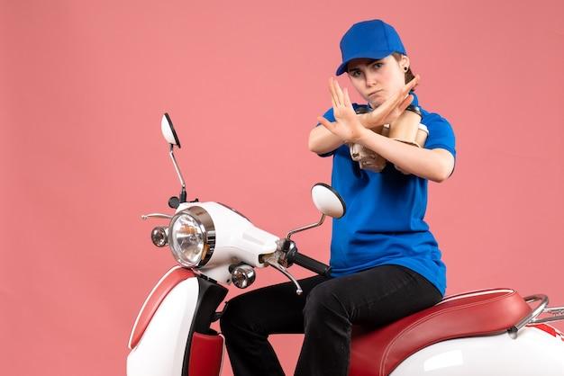 Mensageiro de frente, sentado em uma bicicleta com xícaras de café, no serviço de alimentação de trabalhador de entrega de uniforme cor-de-rosa