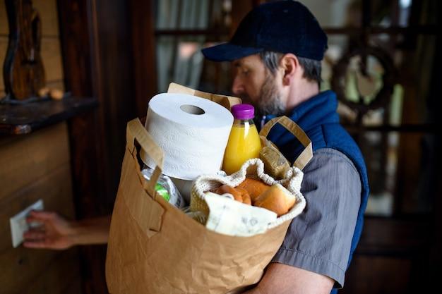 Mensageiro de homem parado na porta da frente e entregando compras, batendo.