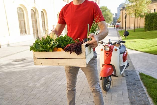 Mensageiro de uniforme segurando uma caixa de supermercado com vegetais frescos