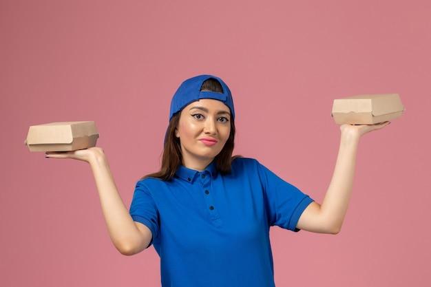 Mensageiro feminino com capa de uniforme azul, vista frontal, segurando pequenos pacotes de entrega na parede rosa.
