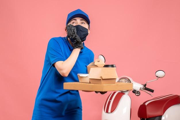 Mensageiro feminino com máscara e entrega de café e comida de frente