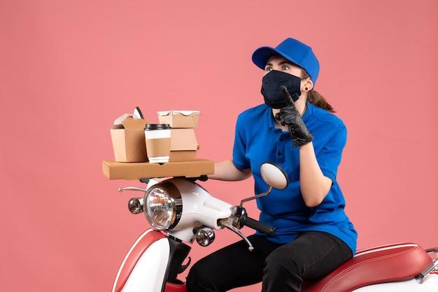 Mensageiro feminino com máscara e entrega de comida na frente
