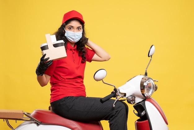 Mensageiro feminino com máscara e xícaras de café em fundo amarelo, uniforme de entrega de serviço secreto de vista frontal