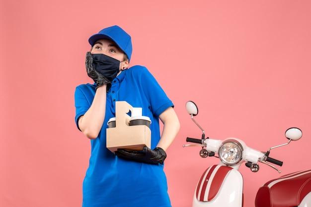 Mensageiro feminino de vista frontal com máscara e entrega de café na rosa