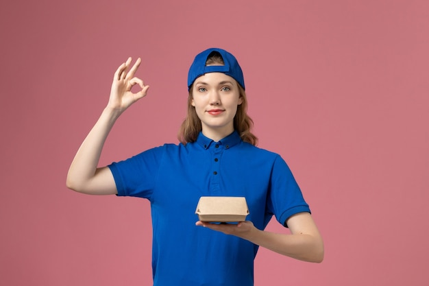 Mensageiro feminino de vista frontal em uniforme azul e capa segurando um pequeno pacote de entrega de comida no fundo rosa.
