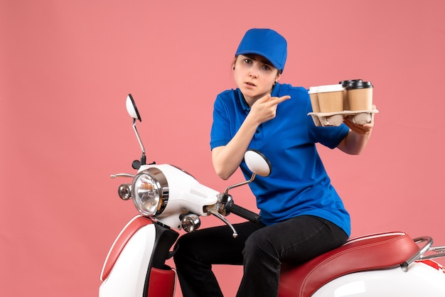 Mensageiro feminino de vista frontal sentado na bicicleta com xícaras de café na cor rosa uniforme trabalho serviço de alimentação de trabalhador
