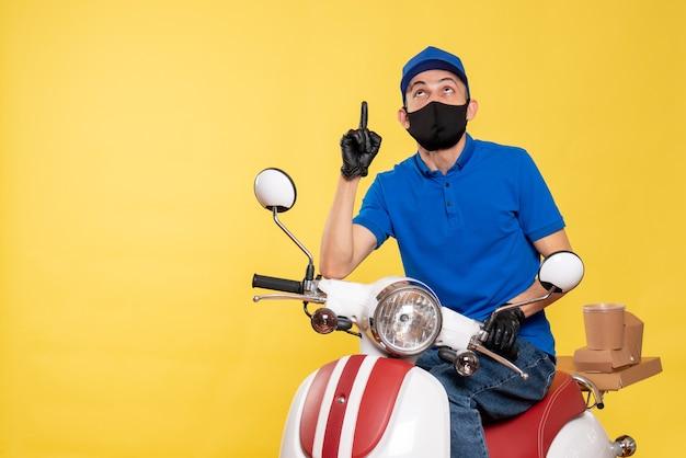 Mensageiro frontal em uniforme azul e máscara sobre um vírus de trabalho de serviço de bicicleta pandêmica de entrega de vírus amarelo