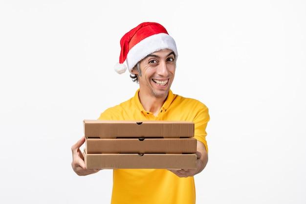 Mensageiro frontal masculino com caixas de pizza na entrega de serviço uniforme de parede branca