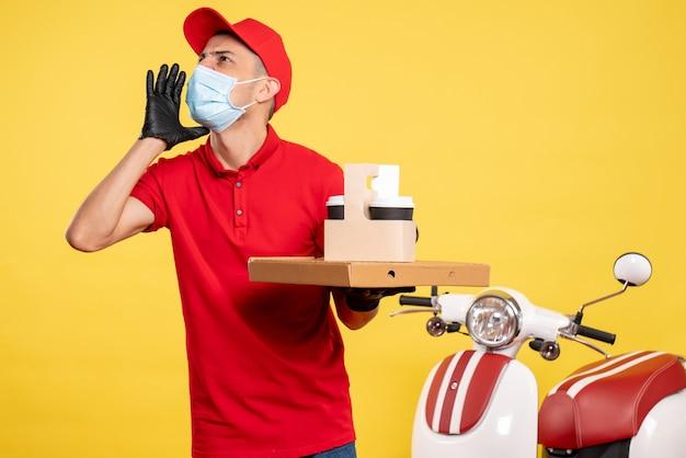 Mensageiro frontal masculino com máscara com entrega de café e caixa na cor amarela serviço de trabalho covid- vírus pandemia de trabalho