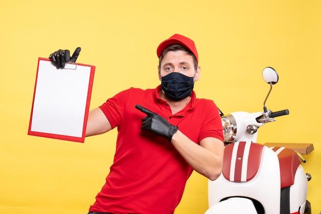 Mensageiro frontal masculino com máscara preta com nota de arquivo no uniforme amarelo, serviço de entrega pandêmica de serviço cobiçado